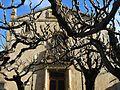 107 Sant Feliu d'Alella, la façana entre els arbres.jpg