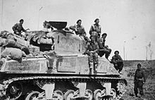 A black and white photograph of a tank; several men in military uniforms are posing standing on the tank