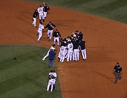 Several men in white baseball jerseys, some wearing black jackets, congregate around second base on a baseball diamond.