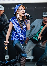 A young Korean female singing on stage wearing a sequined blue hoodie with blue and black tights.