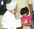 A little girl tying Rakhi to the Prime Minister Dr. Manmohan Singh on the auspicious occasion of 'Raksha Bandhan' in New Delhi on August 30, 2004.jpg