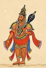A powerfully built figure, probably Bhíma, with a bushy moustache,and Vaishnava namams (emblems) on forehead, arms and chest, rests his huge club on his left shoulder.
