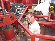 An able seaman uses a needlegun scaler while refurbishing a mooring winch at sea.