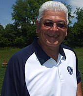 A smiling white tanned man with grey hair, wearing sunglasses and a blue-collared white shirt, outside on a playing field.