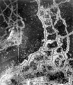 An aerial reconnaissance photograph of the opposing trenches and no-man's land between Loos and Hulluch in Artois, France, taken at 7.15 pm 22 July 1917. German trenches are at the right and bottom, and British trenches are at the top left. The vertical line to the left of centre indicates the course of a pre-war road or track.