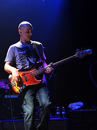 A photograph of a man playing the guitar on stage. He is wearing a t-shirt and jeans.