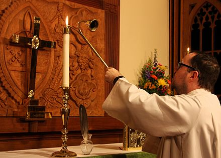 An Episcopal acolyte lighting an altar candle AltarCandleLight.jpg