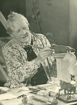 The artist in her late 70s working on the small figurine of a cow