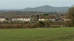 White painted houses with red roofs. In the background is a hill with a tower on it and in the foreground grass and hedgerows