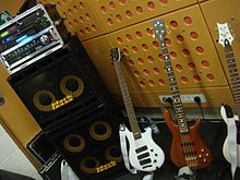 A bass stack has two speaker cabinets (one with four ten-inch loudspeakers and one with two ten-inch loudspeakers). On top of the stacked speaker cabinets is a bass amplifier unit.