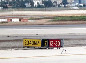 Taxiway - The signs can often be combined, in this case a direction sign, a location sign, and a runway sign