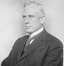 A white-haired man, sitting, wearing dark jacket, patterned tie, and white shirt