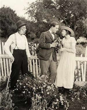 ZaSu Pitts - David Butler and ZaSu Pitts look lovingly at each other while Jack McDonald glares in a scene still for the 1919 silent drama Better Times.