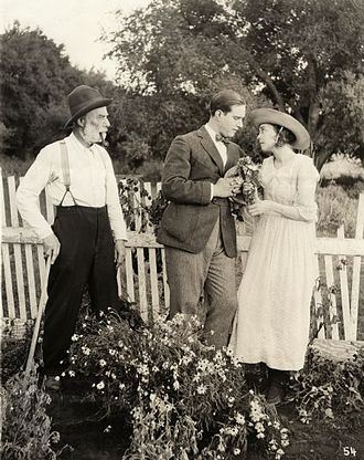 ZaSu Pitts - David Butler and ZaSu Pitts look lovingly at each other while Jack McDonald glares in a scene still for the 1919 silent drama Better Times