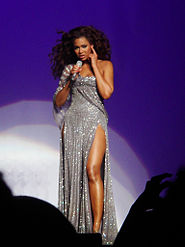 The image of a female who is singing. She wears a long silver dress.