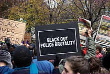 "an Image of a Black Lives matter protest, including a person holding a sign which says ""Black out police violence"""