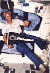 man wearing polo shirt and cargo pants, holding Penn State pennant, background interior of Space Shuttle