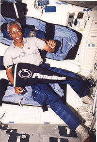Guion S. Bluford, Jr. ombord på Discovery under uppdraget STS-53, hållandes en flagga för Pennsylvania State University.