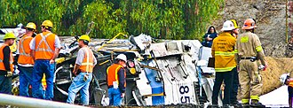 2008 Chatsworth train collision - Recovery workers stand near the rear of the Metrolink locomotive after it was removed from the lead passenger car, where most of the serious injuries and deaths occurred.