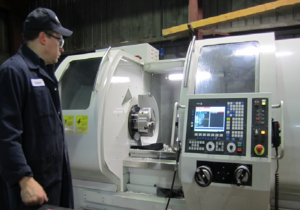 Machinist - Machinist inspecting a CNC lathe
