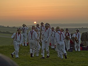 A group of twelve individuals wearing all-white costumes, including hats, are dancing in the centre of a green, grassy space. The low position of the sun indicates that it is early in the morning