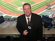 Dan McLaughlin in broadcast booth holding microphone