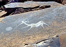 A sandstone slab in horizontal position covered by a dark patina that appears greasy black as if dirtied by touch. In the middle of the slab is a clear white indentation of a fantasy creature with the body of an antelope and the torso and head of a human who appears to b shooting at something with a bow. The figure is surrounded by other engravings that appear geometric and have the color of the slab surface.