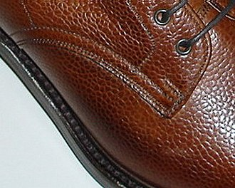 Derby shoe - Detail of a man's derby-style dress shoe showing lacing eyelet tabs sewn on top of the vamp