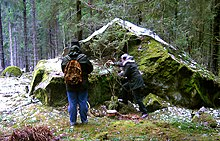 Two people with their backs to the viewer stand in front of a large boulder in the middle of woodland. One of the figures is pouring a liquid onto the ground.
