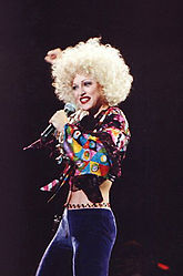 Image of a blond female facing her left. She's wearing purple pants and a maroon blouse with different color squares on the sleeve. She's also wearing an afro hairstyle and with her right arm she holds a microphone to her mouth and has her left arm lifted back above her head.