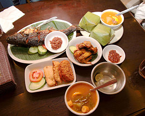 Indonesian cuisine - Example of Indonesian Sundanese meal; ikan bakar (grilled fish), nasi timbel (rice wrapped in banana leaf), ayam goreng (fried chicken), sambal, fried tempeh and tofu, and sayur asem; the bowl of water with lime is kobokan.