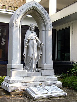 Headstone - Marble headstone of a couple buried together in Singapore, showing an arched emblem, signifying the reunification with one's partner in heaven. Within the arch is a statue of Jesus Christ