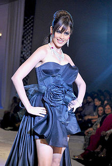 A smiling DiSouza, her hair in a loose bun and long dark bangs, poses on stage in a short, blue, highly styled dress with a thick train.
