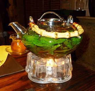 Teapot - Glass teapot containing mint leaves, being warmed by a tealight, Kashgar, Xinjiang, China