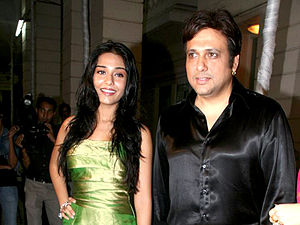 Govinda in a black satin shirt with Amrita Rao, a young actress