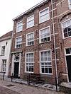 foto van Huis met schilddak en lijstgevel waarin afgeknotte doorgaande pilasterachtige dammen. Eenvoudige witte deuromlijsting met gesneden bovenlicht (eind 18e eeuw). Grijze gebosseerde pleisterlaag