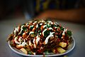 Halal Snack Pack served on ceramic plate, topped with Tablouleh.jpg