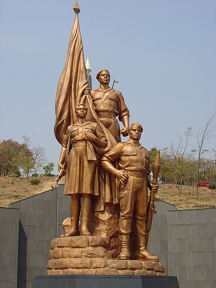 Statues atop the tomb of the Unknown Soldier at Heroes' Acre; the monument was designed by North Korean architects who reported directly to Mugabe Heroes Acre Monument, Harare, Zimbabwe.jpg