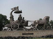 Photograph of a bronze chariot. The discourse of Krishna and Arjuna, in Kurukshetra has been captured in this photo.