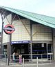 "A dark grey building with a green roof and a rectangular, blue sign reading ""HOUNSLOW EAST STATION"" in white letters all under a blue sky"