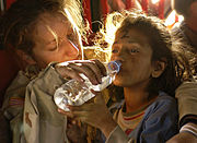 A young girl drinking bottled water.