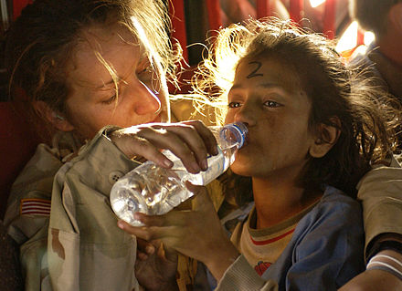 An American soldier gives a young Pakistani girl a drink of water as they are airlifted from Muzaffarabad to Islamabad following the 2005 Kashmir earthquake.