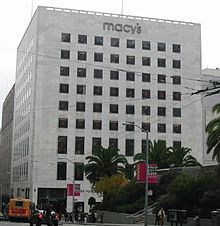 A color photograph of a ten-story retail storefront showing a plain white stone exterior containing eight rows and eight columns of windows set flush with the white stone. Above the windows, the name of the store is shown in lower-case gray letters: Macy's.
