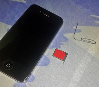 IPhone 4 - An iPhone 4 A1332 with a micro-SIM card removed with a paper clip, showing its SIM card compartment.