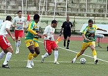 Deux joueurs de football en plein match, un de la JSK l'autre de la JSMB