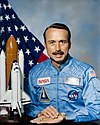 man with mustache in astronaut uniform, model of space shuttle to side, U.S. flag in background