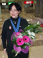 A laughing middle-aged woman with a flower bouquet and a medal around her neck, wearing a Serbia national team tracksuit.