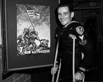 John Bradley (United States Navy) - Bradley standing next to a poster of the second flag-raising on Mount Suribachi, in May 1945