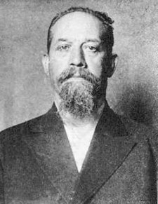 A black and white photograph of a man with short hair and goatee in a suit.