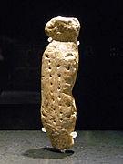 Photographie en couleurs sur fond noir d'une statuette en ivoire représentant un personnage muni d'une tête grossièrement taillée, d'un corps dépourvu de membres et décoré de petites stries horizontales, le tout fixée sur un axe reposant sur un socle en verre.